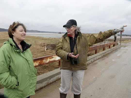 Resident Fran Karr, right, points out to Democratic presidential candidate Sen. Amy Klobuchar, D-Minn., the flooded areas around her home in Pacific Junction, Iowa, on March 29.