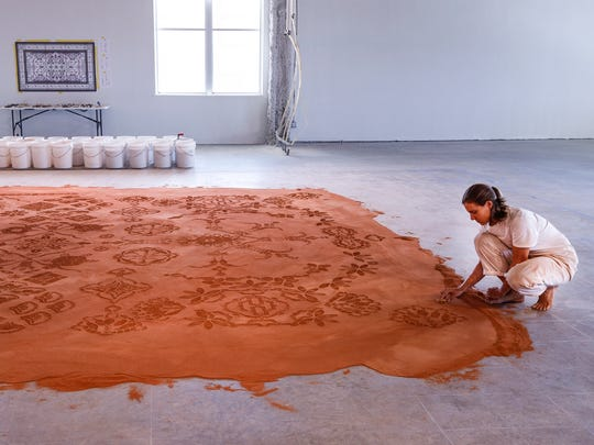 "Artist Rena Detrixhe worked on her piece ""Red Dirt Rug Monument"" last week."