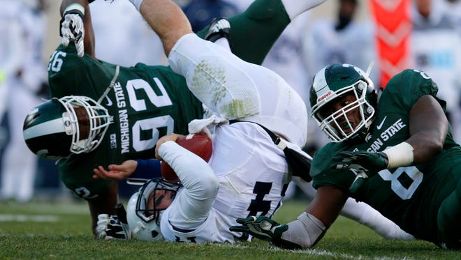 Penn State quarterback Christian Hackenberg, center, is sacked by Michigan State's Joel Heath (92) and Lawrence Thomas, right, during the second quarter of an NCAA college football game, Saturday, Nov. 28, 2015, in East Lansing, Mich.