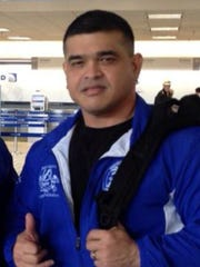 Guam National Fitness Coach Tony Morrison is shown in this 2014 photo traveling with Team Guam for fitness competitions.