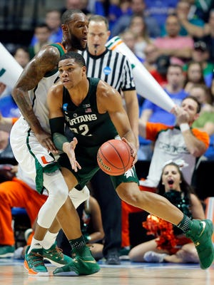Michigan State guard Miles Bridges (22) works for a shot against Miami forward Kamari Murphy, left, in the first half of a first-round game in the men's NCAA college basketball tournament in Tulsa, Okla., Friday March 17, 2017. (AP Photo/Tony Gutierrez)