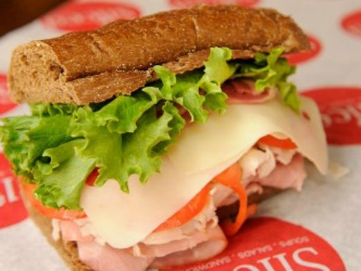Sliced's club has ham, turkey, pancetta, Swiss, lettuce and tomatoes on wheat bread.