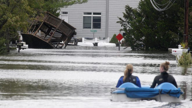 Toms River, N.J., residents use a boat to get back to their house Oct. 30, 2012,?? a day after superstorm Sandy pummeled New Jersey.