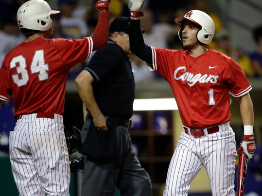 Houston's Landon Appling (1) is greeted by Kyle Survance (34) after Appling scored on an RBI single by Ashford Fulmer in the third inning of an NCAA college baseball regional tournament game against LSU in Baton Rouge, La., Monday, June 2, 2014. (AP Photo/Gerald Herbert)