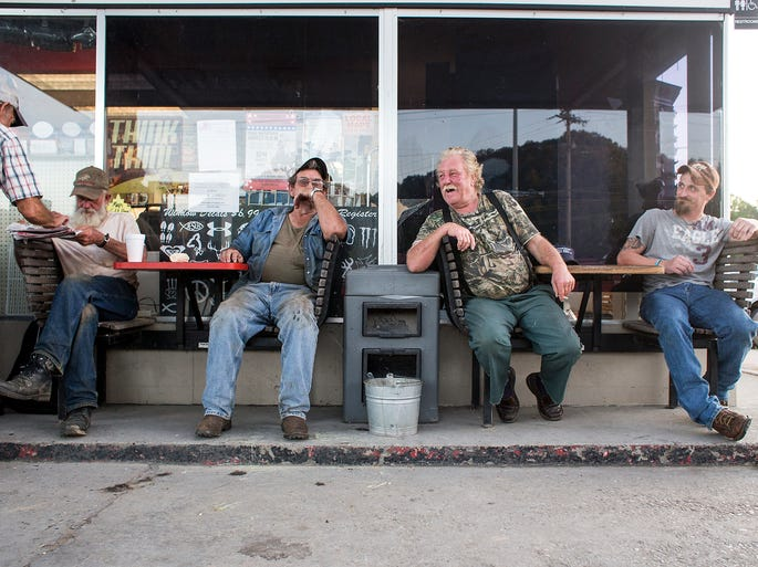 """Tom Orr, left, Joe Waldroup, Roy Grooms and Robert Jordan sit outside Time-Out gas station in Robbinsville Wednesday night, Aug. 27, 2014. Waldroup and Grooms are both former moonshine makers, and Grooms appears on the Discovery Channel show """"Moonshiners"""". They both continue to work construction jobs here and there, they said. """"The smartest people that come from Graham County are the ones who graduated and got out of here,"""" Waldroup said of the county with limited jobs. Robbinsville's main industry, Stanley Furniture, closed in July, putting more than 400 people from the region out of work. 8/27/14"""