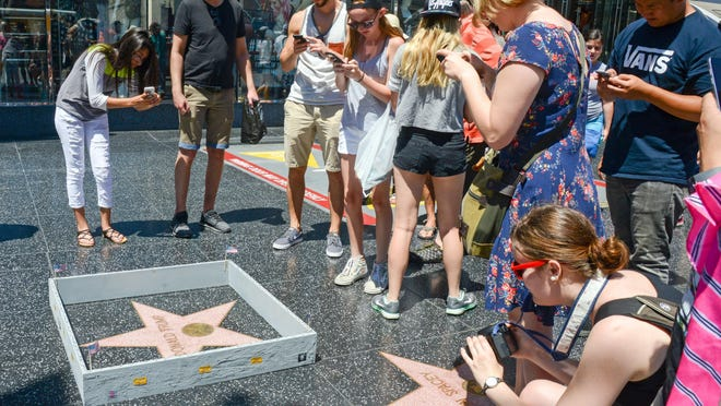 """This Tuesday, July 19, 2016 photo provided by Nick Stern shows a six-inch high, concrete-appearing 'wall,' created by an artist known as Plastic Jesus, surrounding the Hollywood Walk of Fame star of Donald Trump in Los Angeles. It appeared the day the former reality TV star and entrepreneur secured the Republican nomination for president. Tourists snapped photos of the wall, topped with razor wire and plastered with """"keep out"""" signs. The tiny wall was gone by Wednesday morning. (Nick Stern via AP)"""