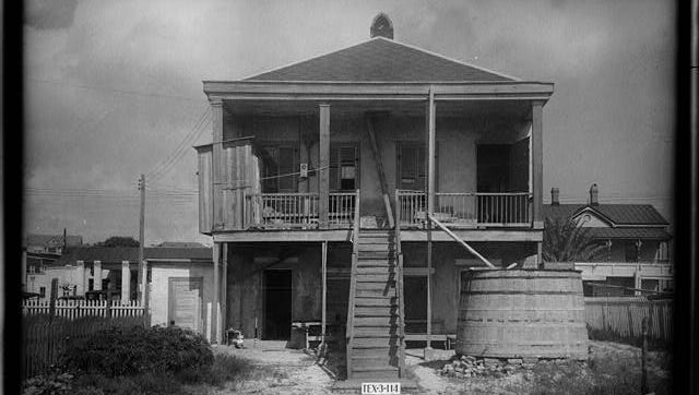 """Rear view of the Conrad Meuly house, in 1936, shows that the back side of a house can be as interesting as the front. This house, like most old homes in Corpus Christi, had its own cistern to store rainwater runoff from the roof. Visible across the street was a rooming house called """"The Chaparral."""""""