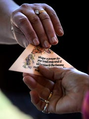 An attendee to the Butterfly in the Park Memorial Service receives a triangular envelope with a sleepy butterfly inside it.  Guests were invited to release a butterfly to honor a loved one who had died.