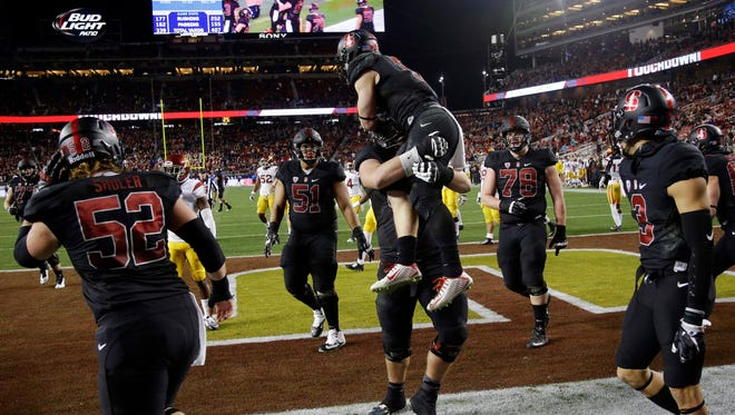 Stanford running back Christian McCaffrey, center, is lifted by a teammate after scoring on a 10-yard run against Southern California during the second half of a Pac-12 Conference championship NCAA college football game Saturday, Dec. 5, 2015, in Santa Clara, Calif.