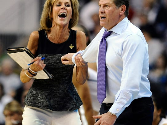 Connecticut women's basketball associate head coach Chris Dailey (left) pulls back head coach Geno Auriemma, right, during the first half of a regional semifinal against Maryland in the 2018 NCAA college basketball tournament in Bridgeport, Conn.