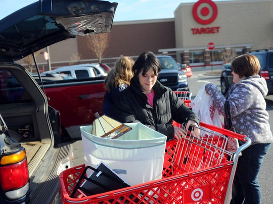 On the last shopping day before Christmas, Halley Litton (center) of Stuarts Draft helps unload three shopping carts filled with items purchased while shopping with Alana Thomas of Stuarts Draft and Holly Henderson of Afton at Target in Waynesboro on Saturday, Dec. 24, 2011.