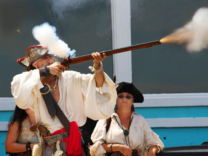 A pirate defending Charlotte Harbor fires his musket during the Fisherman's Village Pirate Fest in Punta Gorda on Saturday.