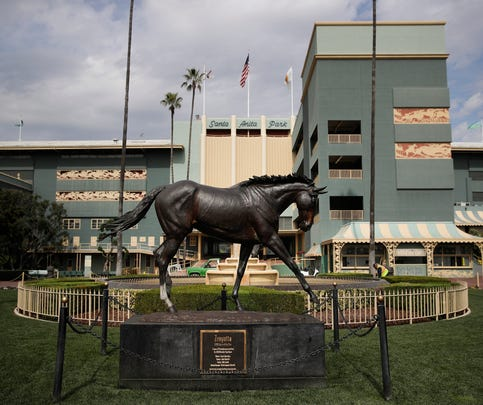 FILE - In this March 5, 2019, file photo, a statue of Zenyatta stands in the paddock gardens area at Santa Anita Park in Arcadia, Calif. An investigation into numerous horse deaths at Santa Anita Park found no criminal wrongdoing but produced a list of recommendations for improving safety at all California racetracks, the Los Angeles County district attorney said in a report Thursday, Dec. 19, 2019. (AP Photo/Jae C. Hong, File)