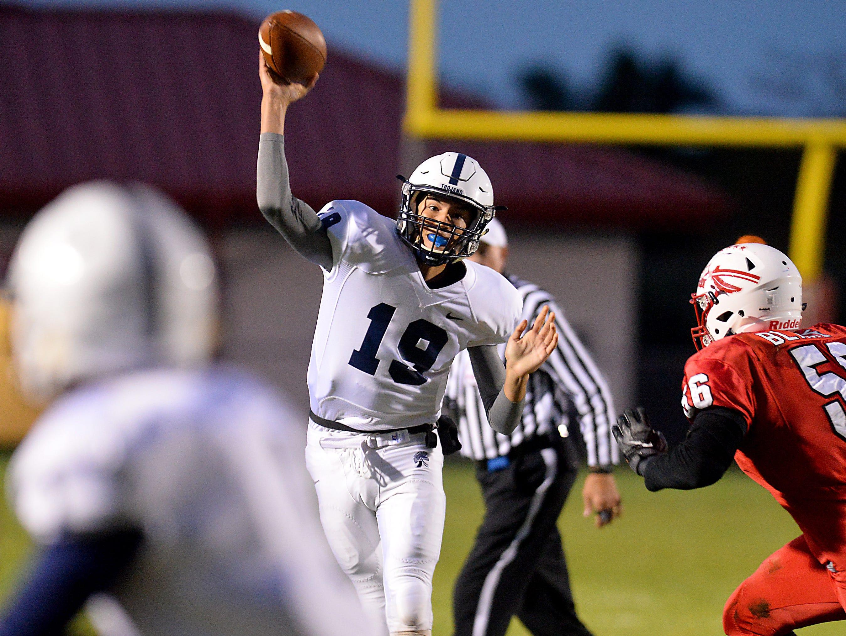 East Lansing quarterback Hunter Helmic passes as Sexton defender Marshon Blake, right, closes in at Sexton Friday.