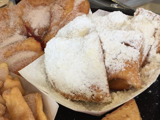 A half-dozen warm, puffy pillows of deep-fried dough, covered in a blizzard of powdered sugar at The Baker Man near Champion Pavilion at the 2018 Indiana State Fair.