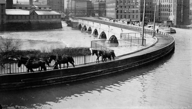 Horses draw a barge across the Genesee River on the Erie Canal aqueduct, in this undated photo. At left, the Kimball Tobacco Factory, which locked out 500 striking workers in 1883.