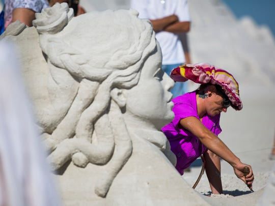 "Melineige Beauregard from Montreal, Canada makes intricate details on her doubles sculpture, ""Lets Meet"", on Sunday, November 27, 2016 at the 30th Annual American Sand Sculpting Championship in Fort Myers Beach, Fla. The ten day event ended Sunday with the advanced amateur national and master sculptors doubles competitions."