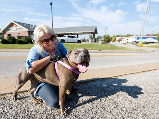 Melissa Schroeder pets her four-year-old pit bull mix Betsy during the Pawsitive Outreach Partnership's Low Cost Vaccination and Pitbull Registration Clinic at Petsway on W. Kearney Street on Saturday, Oct. 14, 2017.