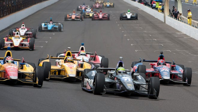 Tony Kanaan, 11, takes the lead on the re-start on lap 198 of the 97th running of the Indianapolis 500.