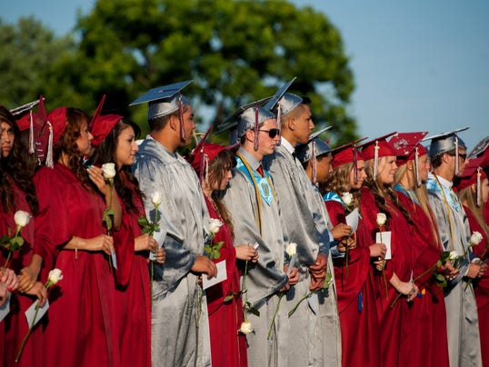 Conewago Valley School District seniors stand during the 2014 graduation ceremony in their maroon and gray robes. Many sports teams in the district wear red, white and blue uniforms. (File -- The Evening Sun)