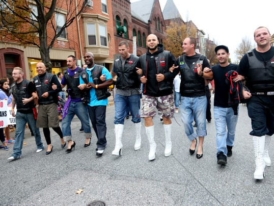 The Twisted Throttle Motorcycle Club of York link together in arms from left; Asher McAlarney, Andre Palmer Sr., Brett Myers, Basil Duncan, Scott Kriskie, Ande Palmer Jr., Sean Hoffman, Shane Thomes and Randy Trowbridge walks down N. Beaver St. towards LSC Design in York to finish the Walk a Mile in Her Shoes during last year's event.