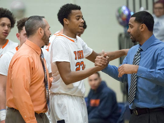 William Penn's Jahaire Wilson celebrates after scoring his 1,000th career point with coaches Troy Sowers, left, and Carmelo Casiano.  Wilson passed the milestone and scored 25 points in William Penn's 82-57 win vs. Spring Grove. (JOHN WHITEHEAD -- FOR GAMETIMEPA.COM)