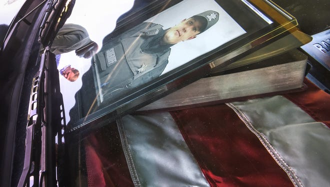 A reflection of Capt. Darrell Hill, left, and Sheriff Chad McBride of the Anderson County Sheriff's Office are in the window of the squad car of fallen deputy Devin Hodges, with photo, flag, and Holy Bible, at the office on Camson Road in Anderson on Friday. The live memorial for people to be able to pay their respects Hodges, who died in a training exercise on Lake Hartwell.