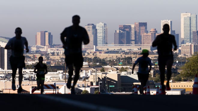 Runners make their way through Papago Park on McDowell Road with the Phoenix skyline in the background during the Rock N' Roll Marathon Arizona in Phoenix, Sunday morning, January 17, 2016.