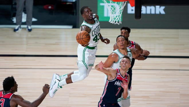 The Celtics' Javonte Green heads to the basket as the Wizards' Jarrod Uthoff (7) defends during the second half at Walt Disney World.