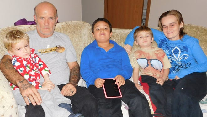The Carroll-Royal Family gather on the couch in their new  home on Webster Street. From left are Logan, 3; Terry Carroll, Melvin, 7; Harley, 5,  and Melinda Royal.