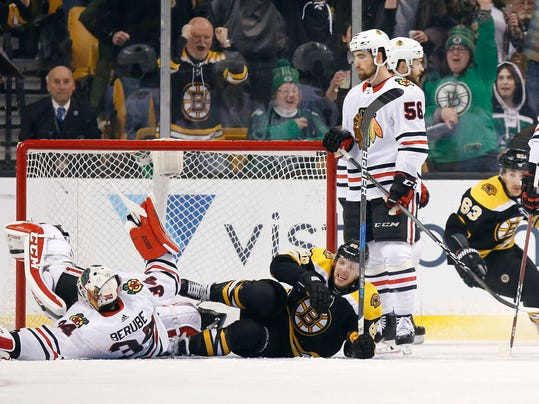 Boston Bruins' David Pastrnak (88), of the Czech Republic, lies on the ice after scoring past Chicago Blackhawks' J-F Berube (34) during the third period of an NHL hockey game in Boston, Saturday, March 10, 2018. The Bruins won 7-4. (AP Photo/Michael Dwyer)