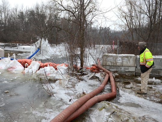 Romke Mersino, of Michels Corporation, keeps an eye on Wolf River water levels while pumping the water away from the intersection of State 47/55 and Menominee County VV in Keshena.