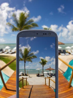 """In a survey, 77 percent of travelers say their phone is either """"very"""" or """"extremely"""" important to have while traveling."""