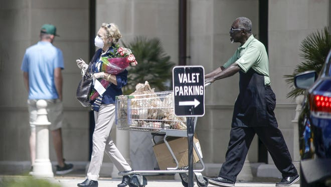 A shopper exits Publix in Palm Beach on Thursday wearing a protective mask and gloves.