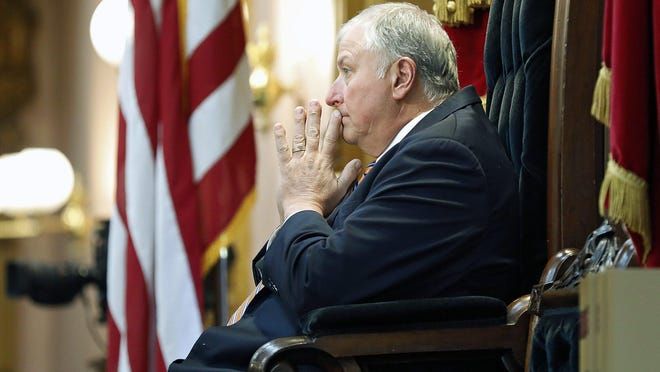 """Larry Householder, shown listening to a state House debate in May before he was deposed as speaker, faces federal criminal charges involving """"dark money."""""""