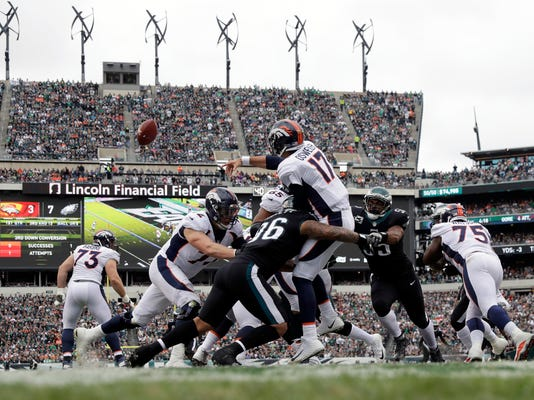 Denver Broncos' Brock Osweiler (17) is hit by Philadelphia Eagles' Derek Barnett (96) during the first half of an NFL football game, Sunday, Nov. 5, 2017, in Philadelphia. (AP Photo/Michael Perez)