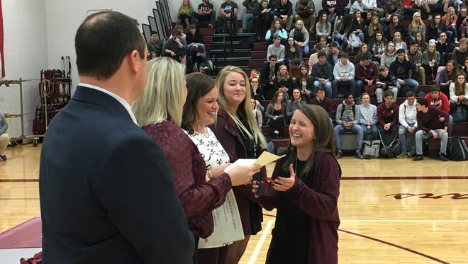 Kelsey Patterson is all smiles as she gets her state championship ring Tuesday at a ceremony honoring the Cougars cheer team for its 2017 state title.