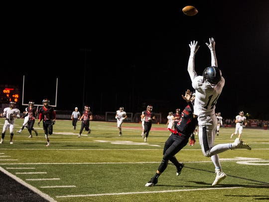 Canyon View High School senior Brayden Lowry (10) goes up for a pass against Hurricane High School faces Friday, September 21, 2018. Canyon View won, 41-27.
