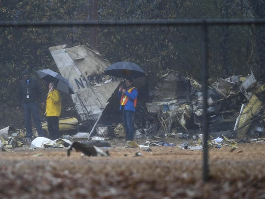 Investigators work the scene of a small plane crash in a city park which killed all on board, Thursday, Dec. 20, 2018, in northwest Atlanta.