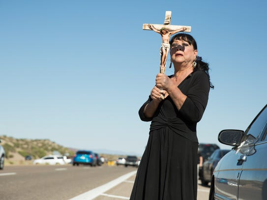 Norma Avilucea-Torres holds up a cross, August 15,