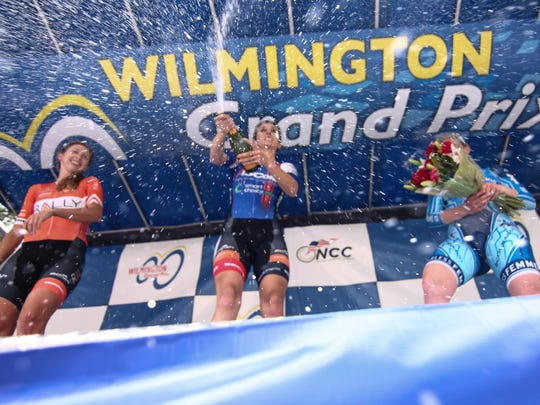 Samantha Schneider, center, of team IS Corp p/b Smart Choice MRI, celebrates on the podium in front of the Grand Opera House after winning the Women's Pro, category I & II (25 miles) race Saturday.
