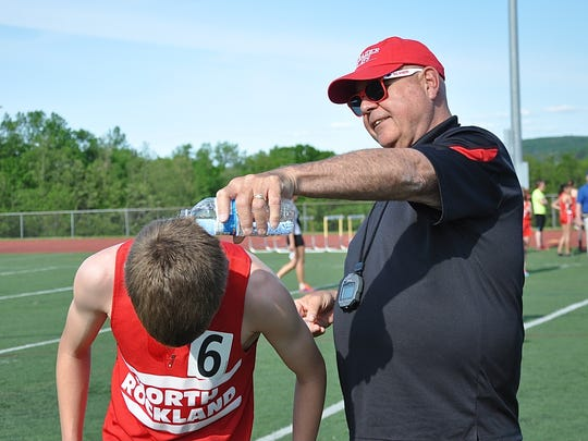 Gene Dall cools off runner Patrick Tuohy after a race while coaching for North Rockland. Dall, who is being inducted into the Rockland County Sports Hall of Fame Thursday, is currently an assistant coach at Texas A&M-Kingsville. Tuohy runs for Fordham University.