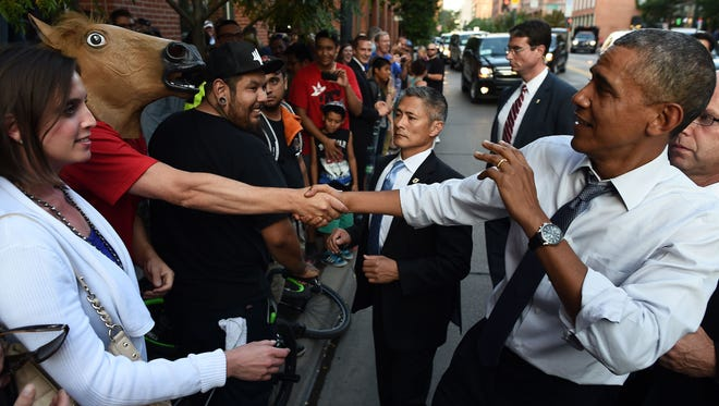 President Obama reacts as he shakes hands with a man wearing a horse head mask on a street in Denver on July 8, 2014.