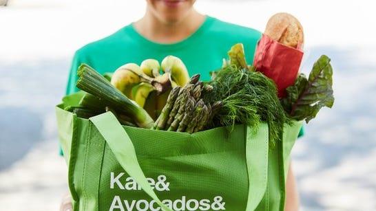 Instacart worker delivering a bag full of groceries