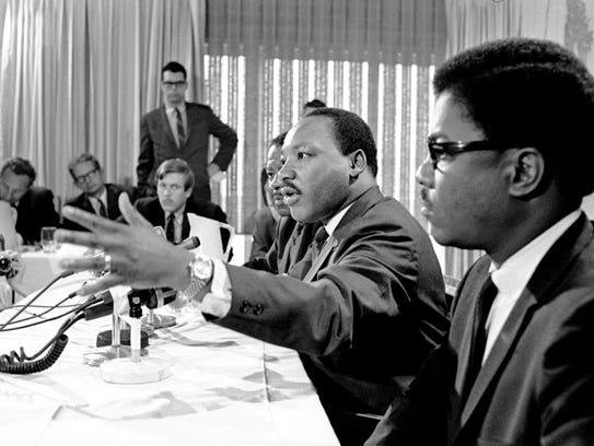 Martin Luther King Jr. talks with reporters at the