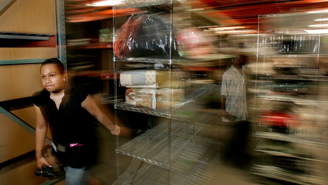 Yvolla Filimoeatu gathers merchandise off the shelves for shipment at the Overstock.com warehouse in December 2006, in Salt Lake City, Utah.