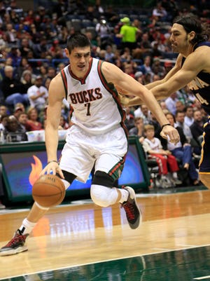 Milwaukee Bucks forward Ersan Ilyasova, left, drives to the basket against Indiana Pacers forward Luis Scola, right, during the first half of an NBA basketball game Thursday in Milwaukee.