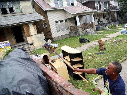 Omar Peterson sweeps up small items that were falling out of the dumpster from abandoned homes on Waverly Street on Aug. 2, 2014, as part of ARISE Detroit!'s beautification efforts.