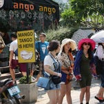 In this March 30, 2014 photo, Chinese tourists, facing camera, buy tickets for a tour to Chiang Mai University in Chiang Mai province, northern Thailand.