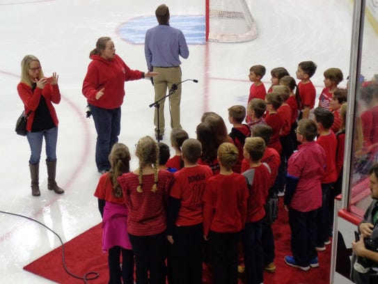 4th/5th grade chorus director Kristen Burkhart directs BRES students singing the Star-Spangled Banner at the Oct. 21 Binghamton Devils hockey game.  Principal Danelle Decker (pictured left) also joined the students on the ice.